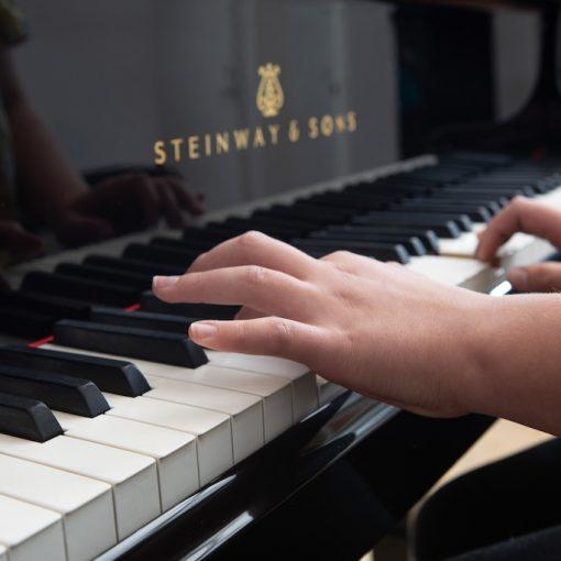 Pianonsoittajan kädet koskettimilla